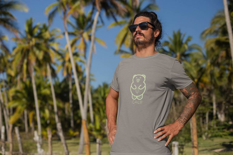 cali-avo-t-shirt-worn-by-a-tattooed-man-standing-by-palm-trees